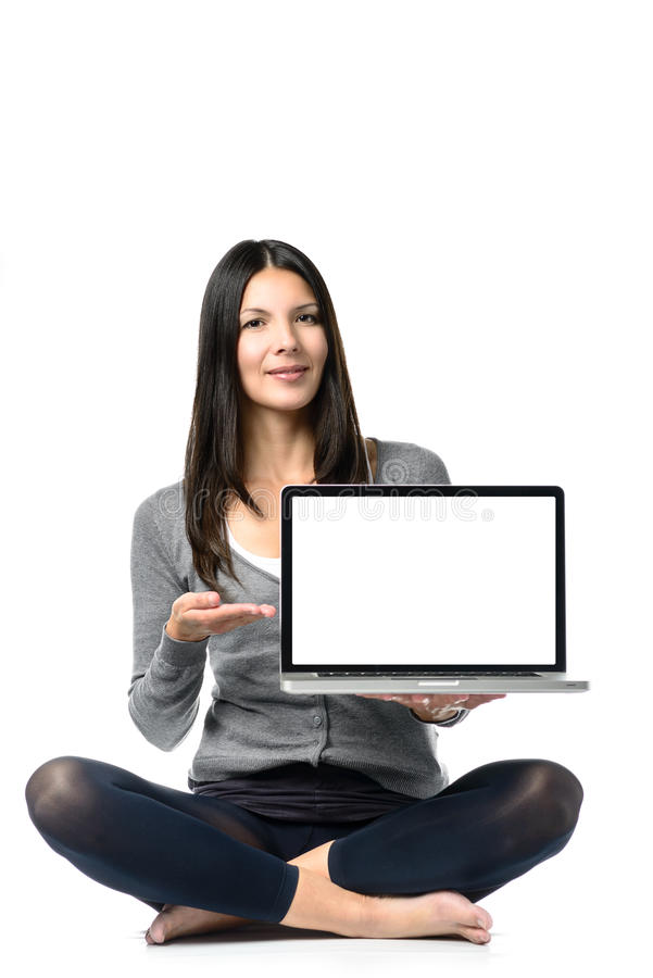 Woman Sitting on Floor Showing Laptop on Hand. Young Pretty Woman Sitting on Floor with Crossed Legs Advertising Brand New Laptop Computer on Hand. Isolated on stock photo