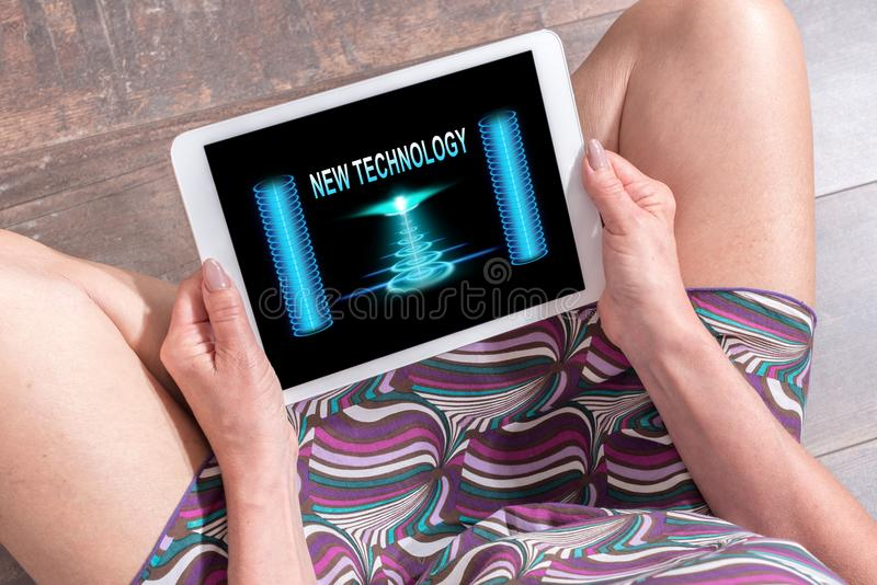 New technology concept on a tablet. Woman sitting on the floor with a tablet showing new technology concept royalty free stock photography