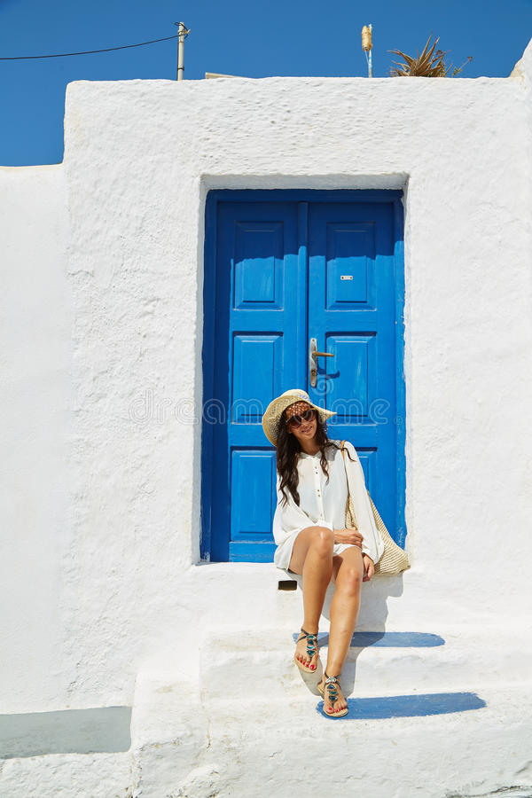 Woman sitting in front of a blue vintage entrance door stock photo