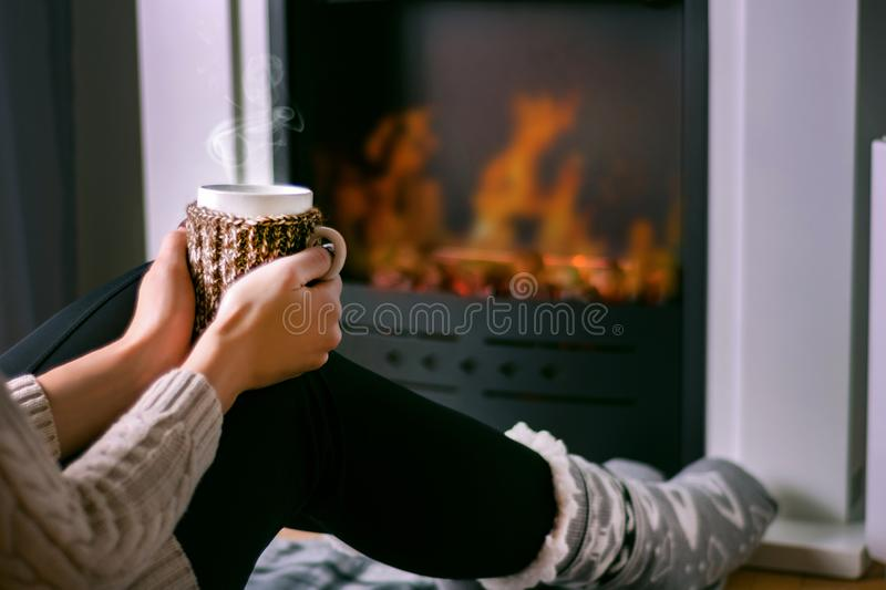 Woman sitting in front of the fireplace and holding cup of tea in hand on legs. Young girl sitting in front of the fireplace and holding cup of tea in hand on royalty free stock photos