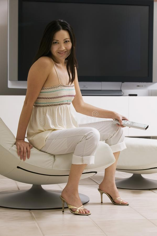 Woman sitting in front of large flat screen tv stock photos