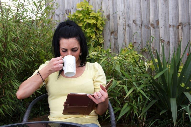 A woman sitting in the garden reading stock photos