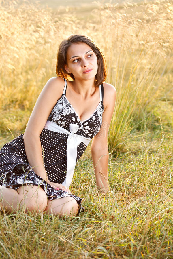 Woman sitting on the grass stock photos