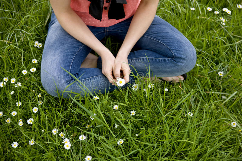 A woman sitting in the grass cross-legged, holding a daisy royalty free stock photography