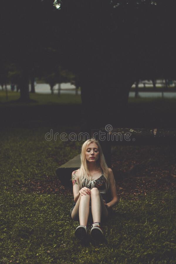 Woman sitting in grass at park stock photography