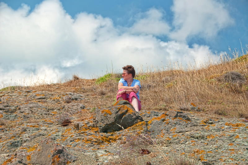 Woman sitting in grasses on hill stock photography