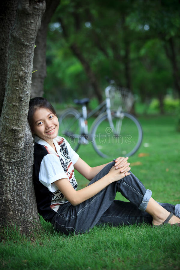Woman Sitting In The Green Garden With Bicycle Bac Stock Photo