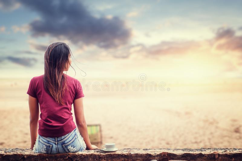 Women sitting on the ground near the beach with sunset time and nice cloud. royalty free stock photography