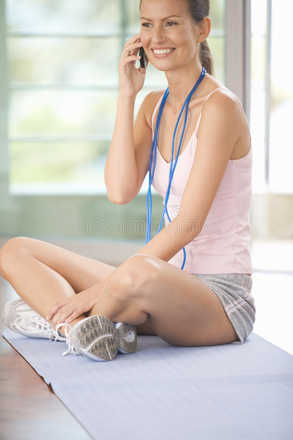 A woman sitting in a gym stock photography