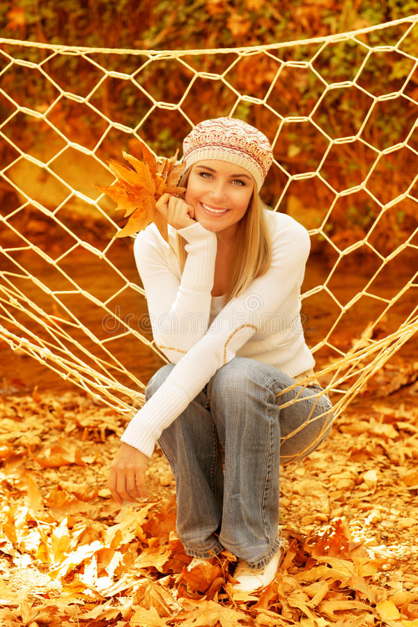 Woman sitting in hammock. Picture of cute female swinging in hammock in autumnal park, closeup portrait of pretty woman relaxed on backyard, attractive blond stock image