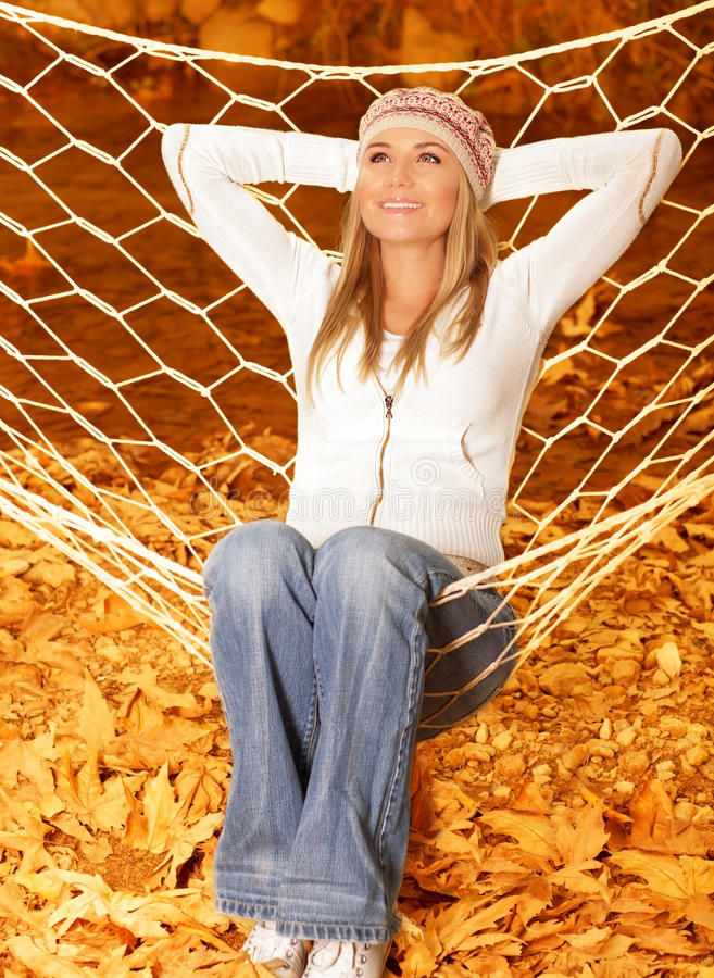 Woman sitting in hammock. Image of cute girl swinging in hammock on backyard in warm autumn weather, pretty female sitting on swing and enjoying beautiful fall royalty free stock photos