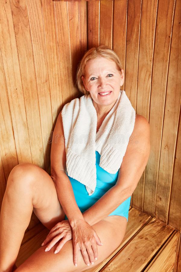 Woman is sitting happily in the sauna stock photo