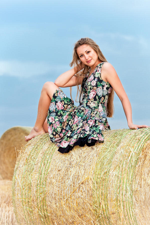 Woman sitting on hay bale. Woman having fun sitting on hay bale royalty free stock images