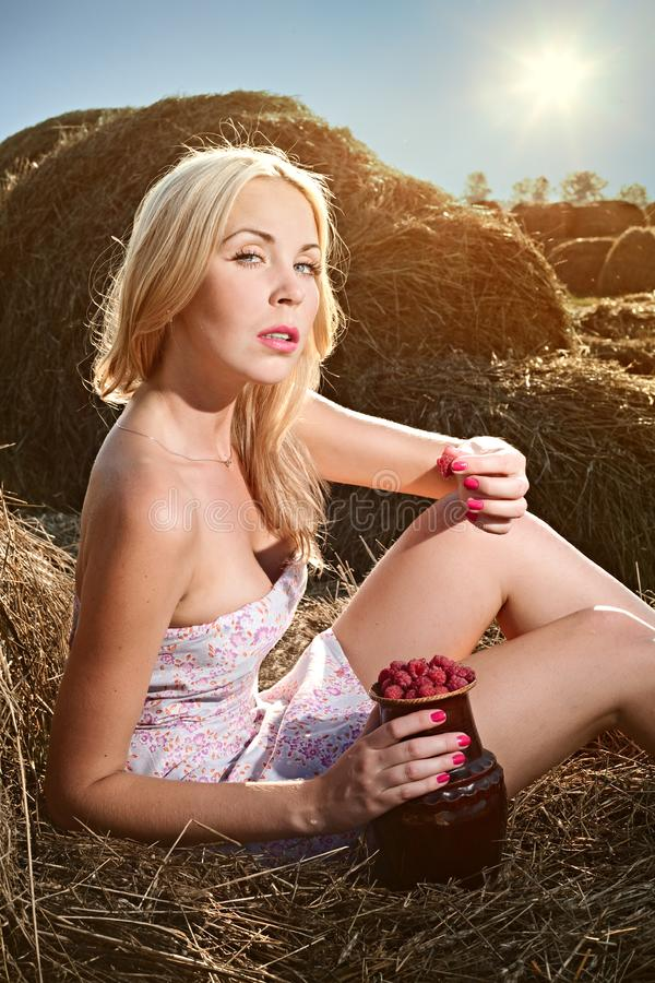 Download Woman Sitting On The Hay And Eat Raspberries Stock Photo - Image of flow, beautiful: 15921588