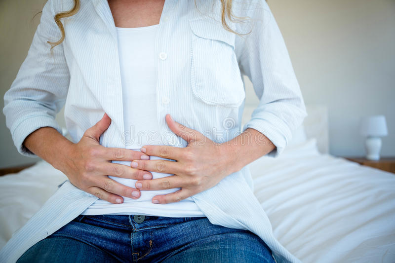 woman sitting on her bed clutching her stomach stock photography