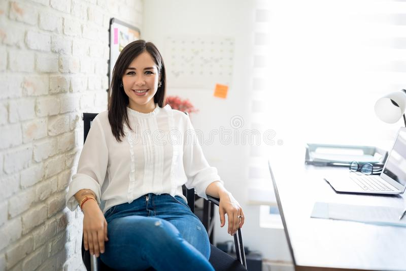 Woman sitting at her desk. Portrait of beautiful young latin woman sitting relaxed on her office chair making an eye contact royalty free stock image