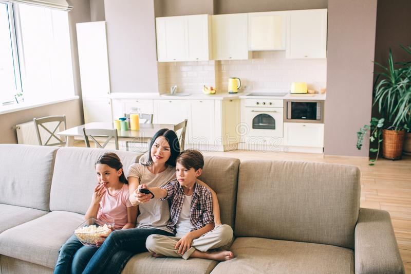 Woman is sitting with her kids and looking straight. Girl eats popcorn. Boy is using remote control from TV. Woman holds royalty free stock photo