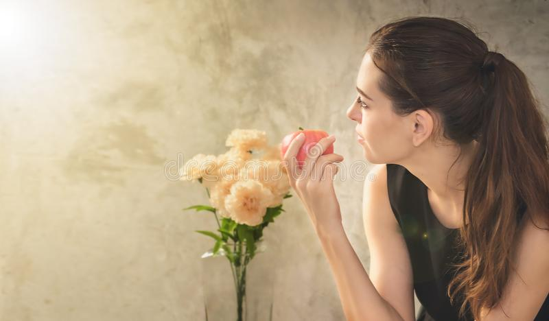 The woman is sitting and holding an apple in her hand.This image stock photography