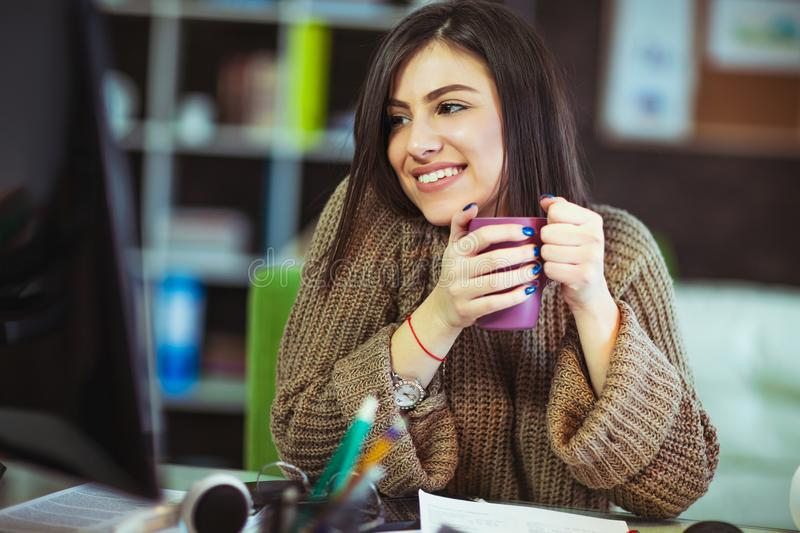 Woman sitting in home office at desk stock image