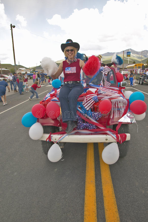 Woman sitting on the hood of a jeep decorated for the Fourth of July, in Lima Montana stock photography