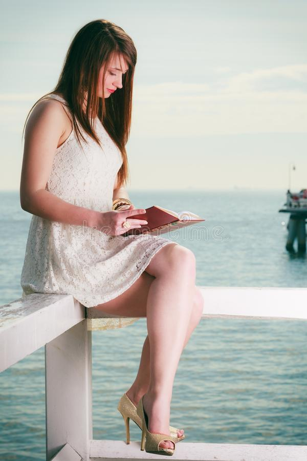 Woman sitting on hurdle near sea, reading book royalty free stock images