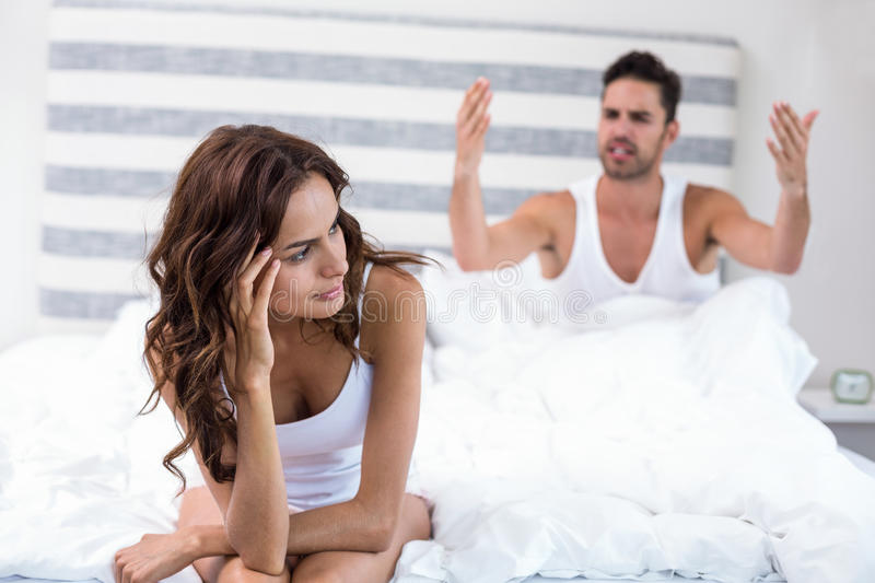 Woman sitting while husband shouting at her royalty free stock image