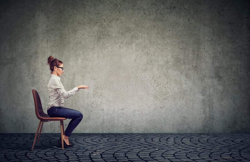 Woman sitting at imaginary table. Side view of an employee woman in glasses sitting at invisible table pretending to type on computer stock photography