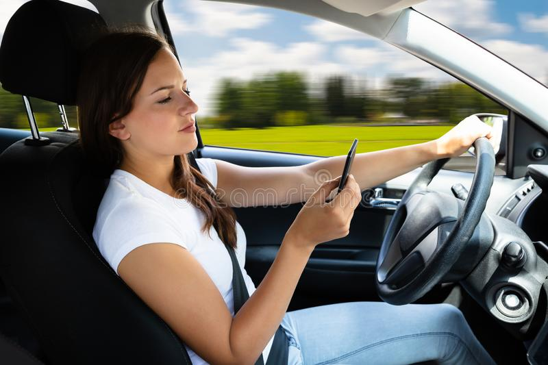 Woman Sitting Inside Car Typing Text Message On Cellphone stock photography