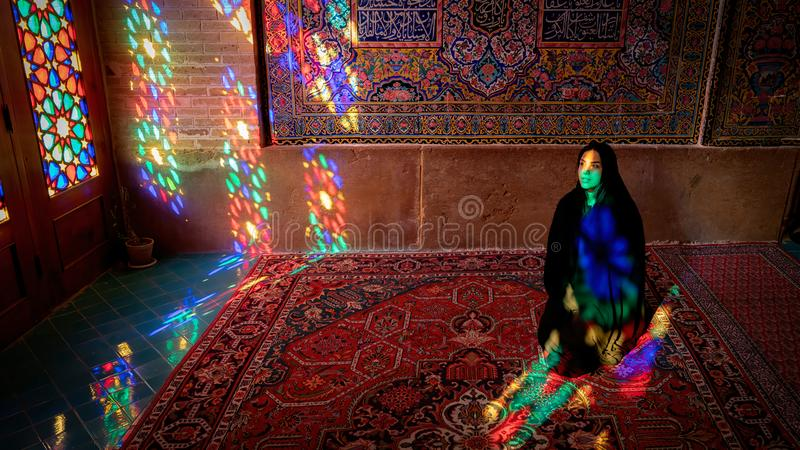 Woman sitting inside with stained glass window reflections of Nasir al-Mulk Mosque, Shiraz, Iran. Iran, Shiraz - May 2019: Woman sitting inside with stained royalty free stock photos