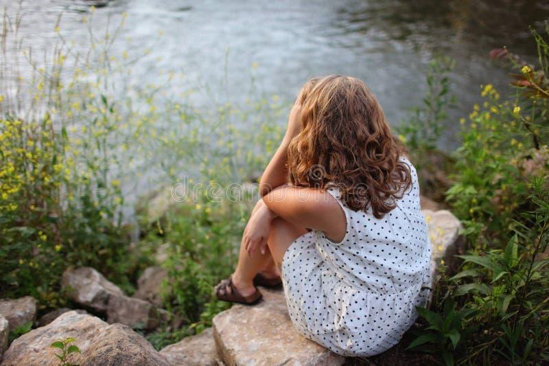 Woman Sitting by Lake stock photography