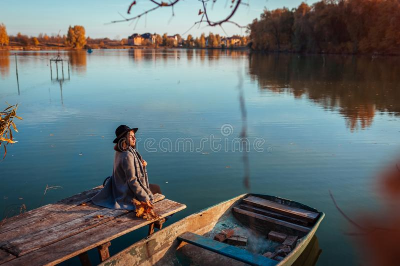 Woman sitting on lake pier by boat admiring autumn landscape. Fall season activities stock image