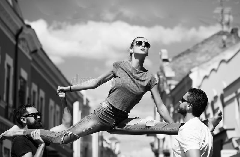 Woman sitting leg split on shoulders of two men. Woman or girl, stylish, fit model, in sunglasses and blue jeans sitting leg split on shoulders of two bearded stock images