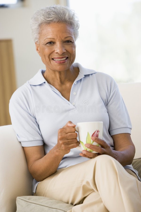 Woman Sitting In Living Room With Coffee Smiling Royalty Free Stock Image