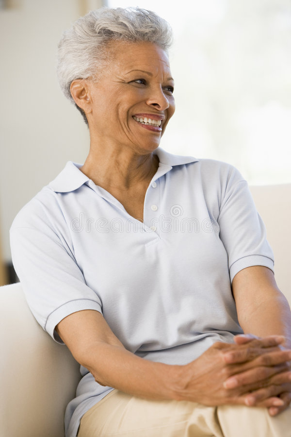Woman Sitting In Living Room Smiling Royalty Free Stock Image