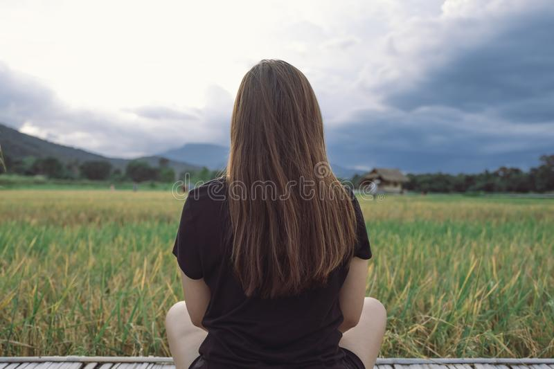 A woman sitting and looking at a beautiful rice field onward with feeling relaxed. And calm royalty free stock image