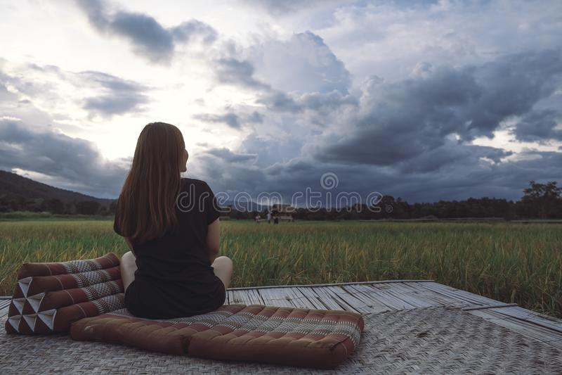 A woman sitting and looking at a beautiful rice field onward with feeling relaxed. And calm stock photography