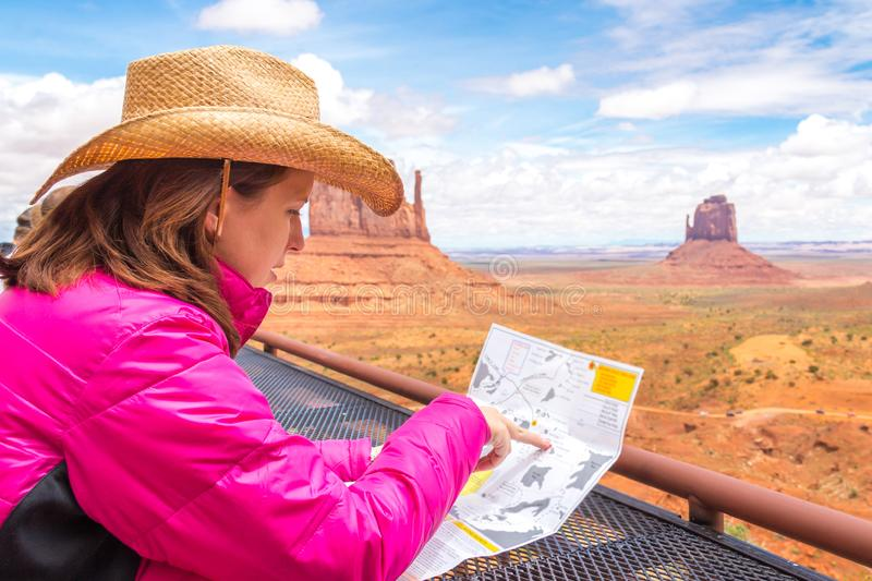 Woman sitting and looking at map in Monument Valley with red rocks overview in Arizona USA. Woman wearing cowboy hat sitting and looking at map in Monument royalty free stock photo