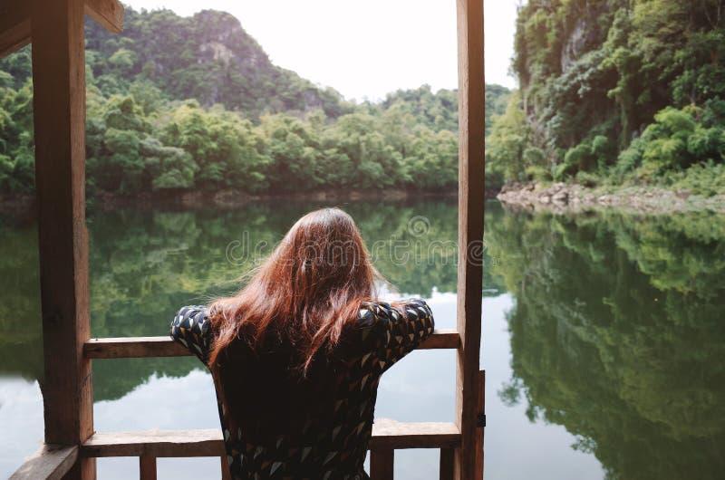 Woman sitting and looking at nature lake stock photo