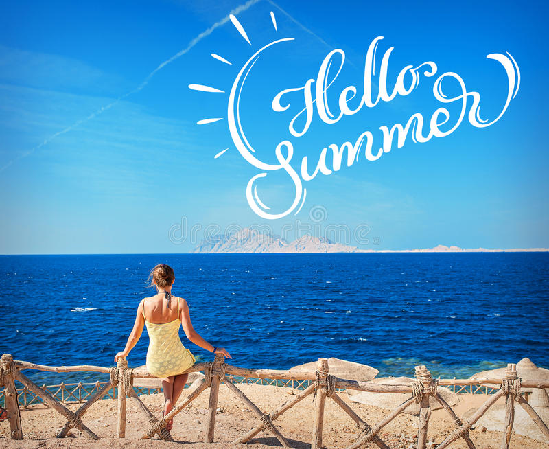 Woman sitting looking at the sea and text Hello Summer. Calligraphy lettering.  stock photo