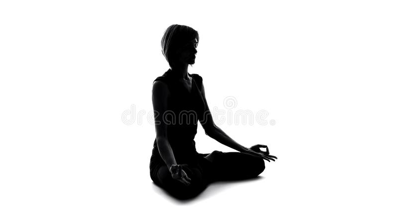 Woman sitting in lotus pose and meditating, finding yoga peace, namaste gesture royalty free stock photo