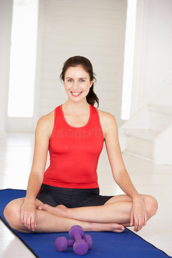 Woman sitting in lotus position. On yoga mat inside smiling at camera royalty free stock photography