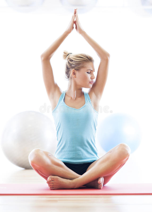 Woman sitting in lotus position. Eyes closed royalty free stock images