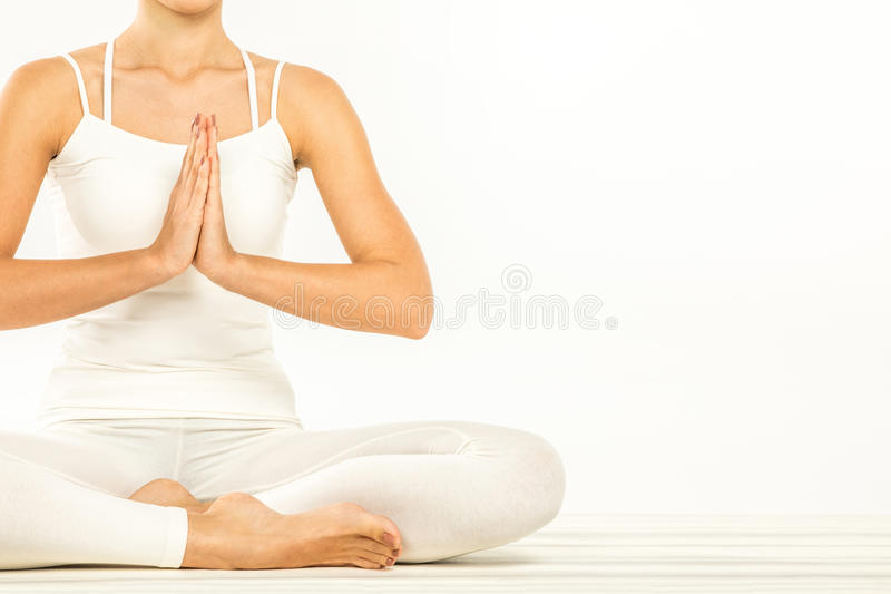 Woman sitting in lotus position. With Namaste Mudra gesture on white stock images