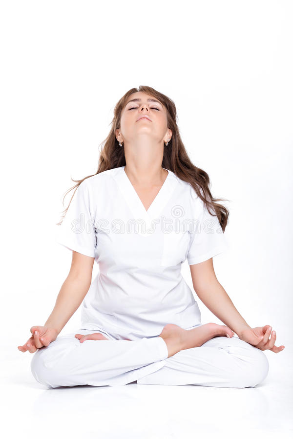 Woman sitting in the Lotus position. Young woman in a white suit sitting in the Lotus position. the doctor meditates royalty free stock photography