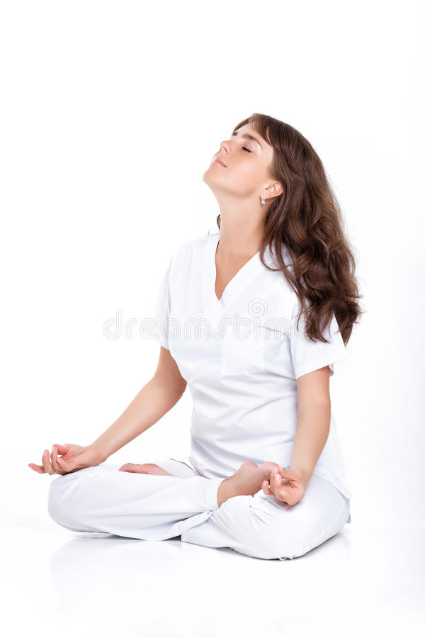 Woman sitting in the Lotus position. Young woman in a white suit sitting in the Lotus position. the doctor meditates stock photography
