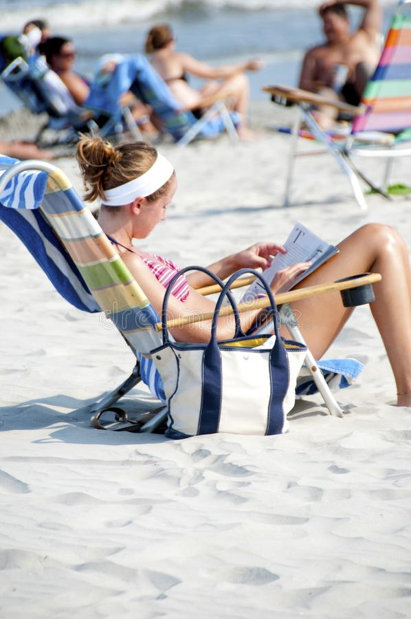 Woman Sitting on the Lounge Chair Reading Magazine on the Beach during Nighttime stock photography