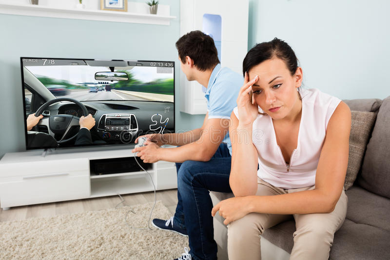 Woman Sitting Beside A Man Addicted To Videogame royalty free stock photography