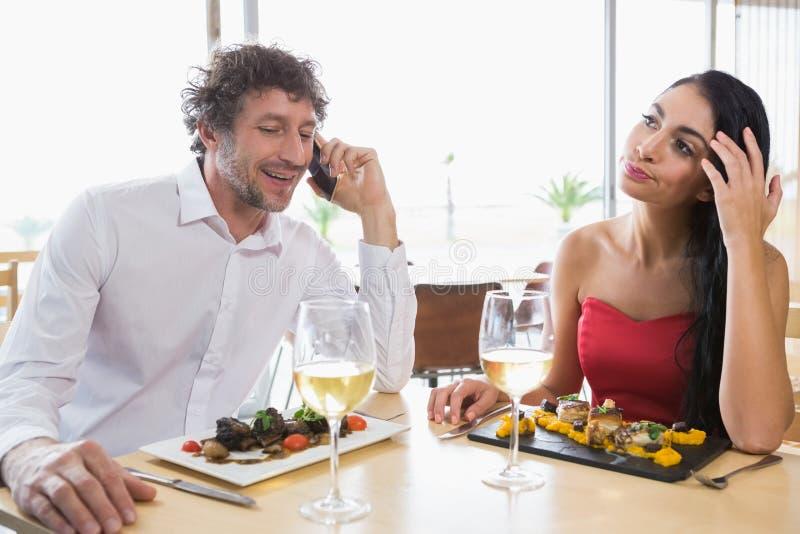 Woman sitting while man talking mobile phone stock image