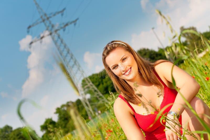 Woman sitting in meadow or field stock photo