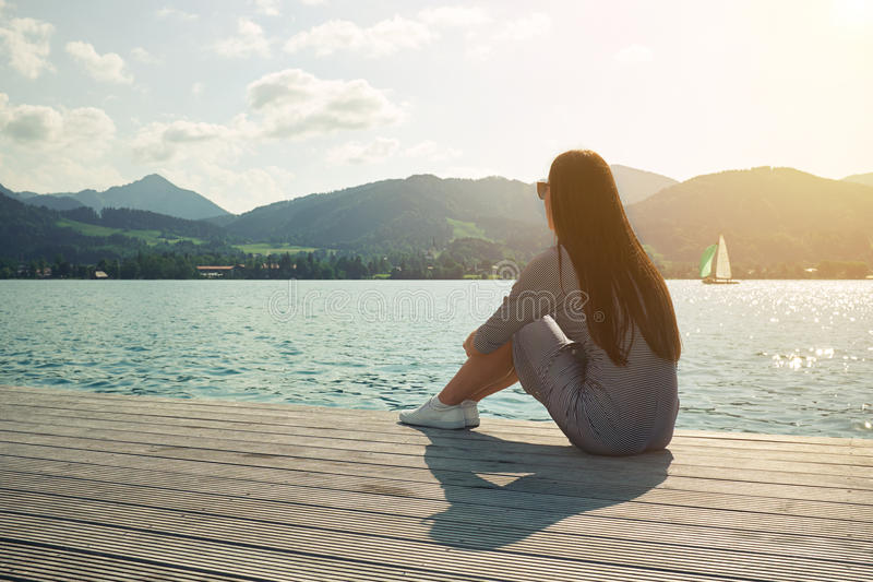 Woman sitting on the moorage. Young woman sitting on the moorage and looking at beautiful view stock images